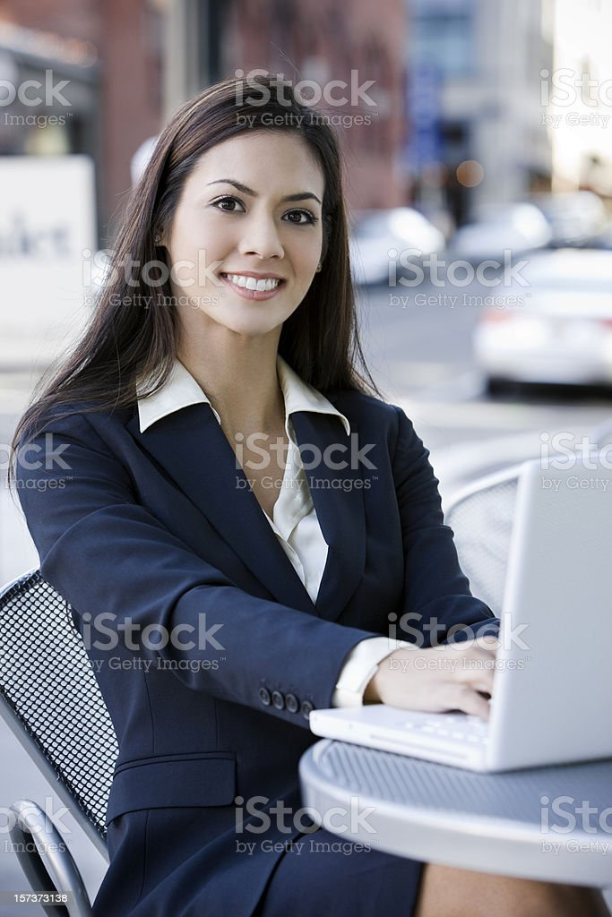Beautiful Brunette Businesswoman Using Laptop at Downtown Cafe royalty-free stock photo