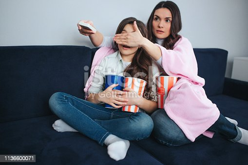 Beautiful brunette caucasian mother and daughter sit together in room. Mom covered eyes of girl. She hold remote controll and look forward with disgust. Daughter hold bakset popcorn and coke