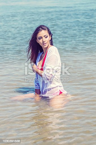 istock Beautiful brunette Caucasian woman relaxing in shallow water Fashion portrait Summer time Sunny day 1030391558
