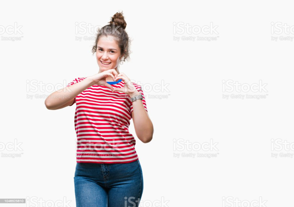 Beautiful brunette curly hair young girl wearing casual look over isolated background smiling in love showing heart symbol and shape with hands. Romantic concept. stock photo