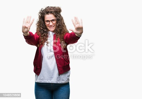 Beautiful brunette curly hair young girl wearing jacket and glasses over isolated background showing and pointing up with fingers number nine while smiling confident and happy.