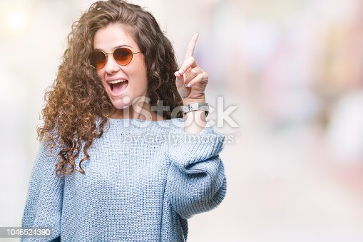 Beautiful brunette curly hair young girl wearing sunglasses over isolated background pointing finger up with successful idea. Exited and happy. Number one.