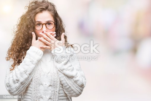 Beautiful brunette curly hair young girl wearing winter sweater over isolated background shocked covering mouth with hands for mistake. Secret concept.