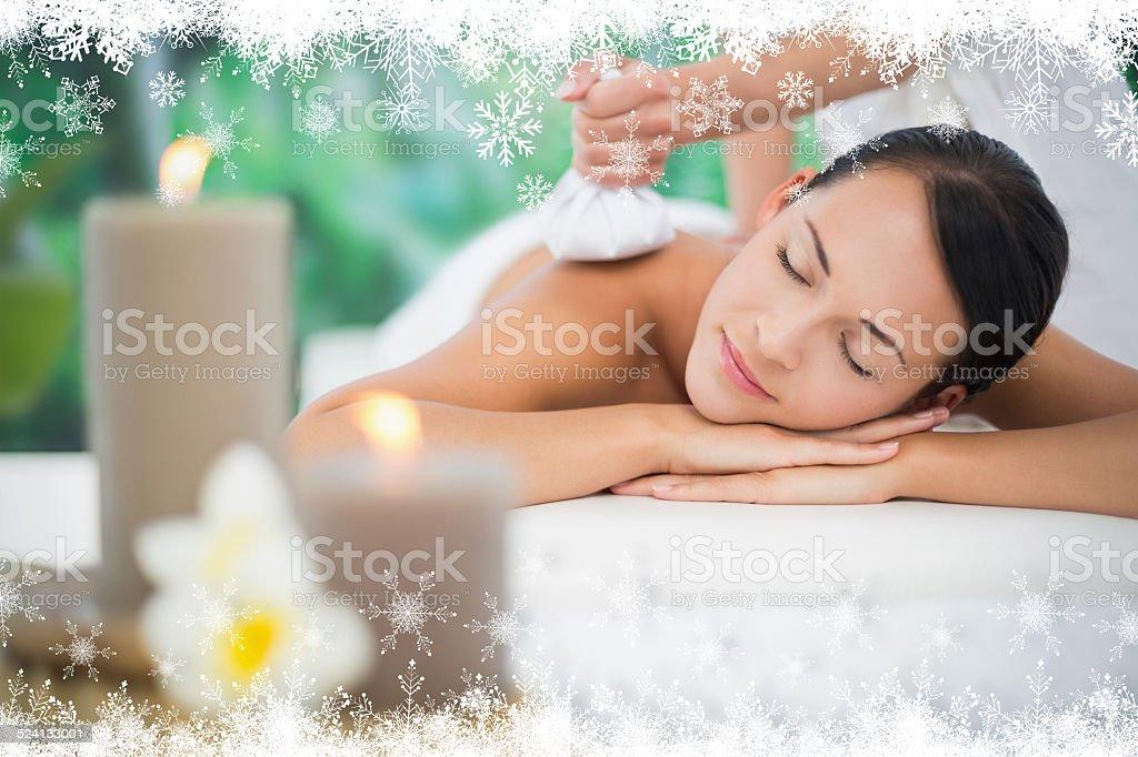 Beautiful brunette enjoying a herbal compress massage stock photo