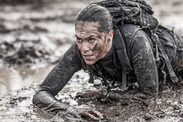 beautiful brunette female military swat security anti terror agent crawling during operations in muddy sand - warrior person stock pictures, royalty-free photos & images
