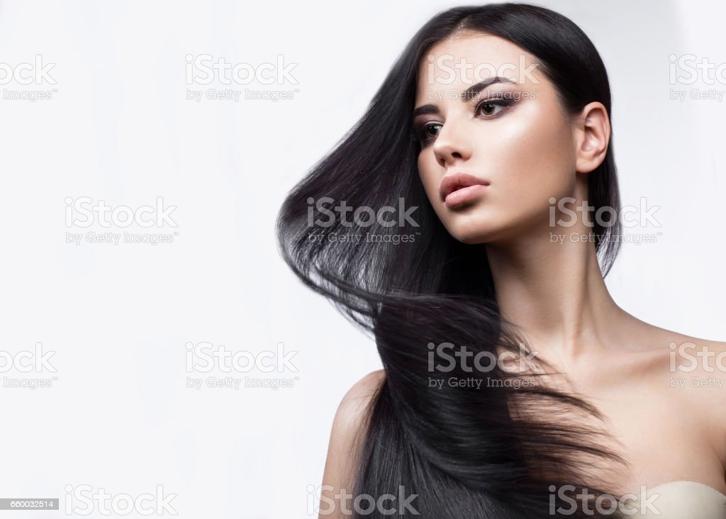 Beautiful brunette girl in move with a perfectly smooth hair, and classic make-up. Beauty face. stock photo