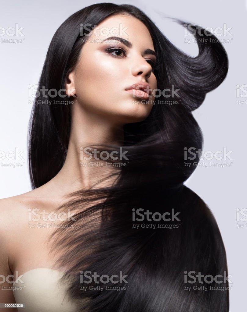 Linda menina morena em mover-se com um cabelo perfeitamente liso e make-up clássico. Rosto de beleza. - foto de acervo