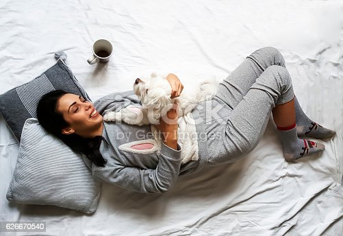 beautiful brunette girl lying and cuddling her cute dog on bed and smiling