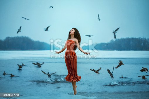 Beautiful young brunette woman flies with the birds. Background shore of a frozen river. She is wearing a beautiful orange dress. Sad face with a glimmer of hope to escape from the routine of everyday life. Fantasy photo, creative color