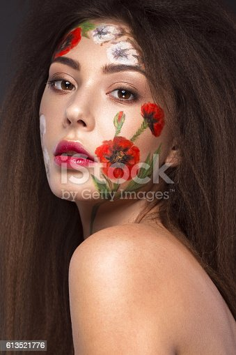 istock Beautiful brunette girl with curls and a floral pattern on 613521776