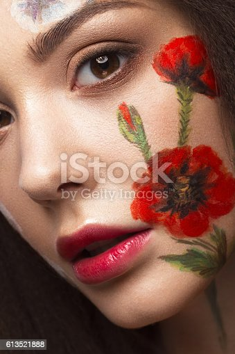istock Beautiful brunette girl with curls and a floral pattern on 613521888