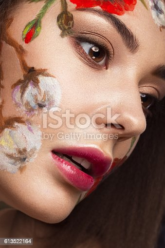 istock Beautiful brunette girl with curls and a floral pattern on 613522164