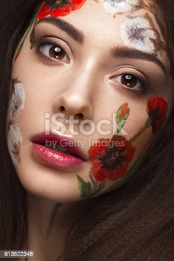 istock Beautiful brunette girl with curls and a floral pattern on 613522348