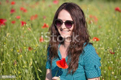 34b5c45675 692948228istock Hermosa chica morena con gafas de sol agradables en Prado  de la flor de Amapola