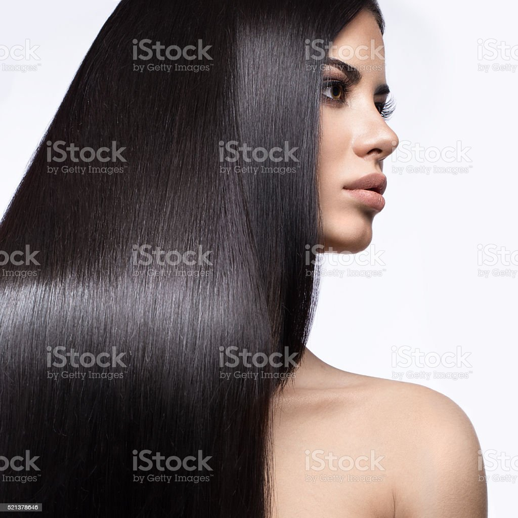 Beautiful brunette girl with  perfectly smooth hair, and classic make-up. stock photo