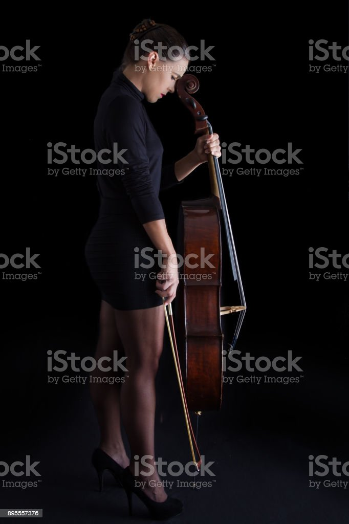 Beautiful Brunette Holding A Cello With Selective Light In Black