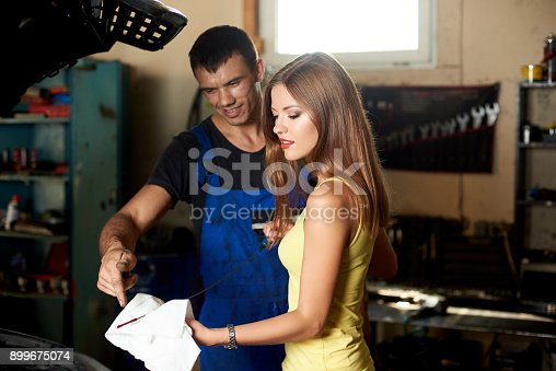 962888586 istock photo A beautiful brunette holding a dipstick to check the engine oil the mechanic tells her, both are standing near the open hood of the car in the garage 899675074