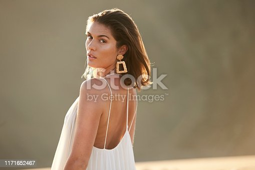 Beautiful brunette in sunlit desert, looking at camera
