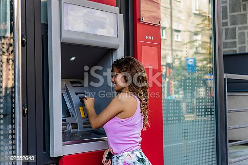 945598452 istock photo Beautiful Brunette Inserting a Credit Card to ATM Machine 1162552643