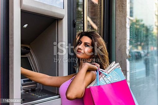 945598452istockphoto Beautiful Brunette Inserting a Credit Card to ATM Machine 1162553357