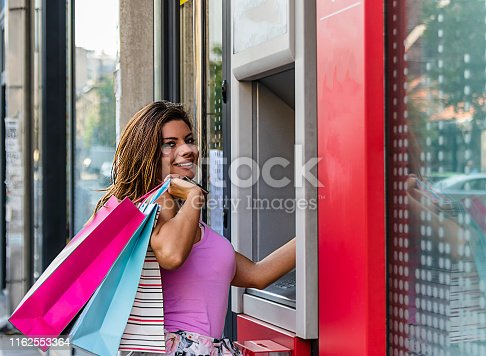 945598452istockphoto Beautiful Brunette Inserting a Credit Card to ATM Machine 1162553364