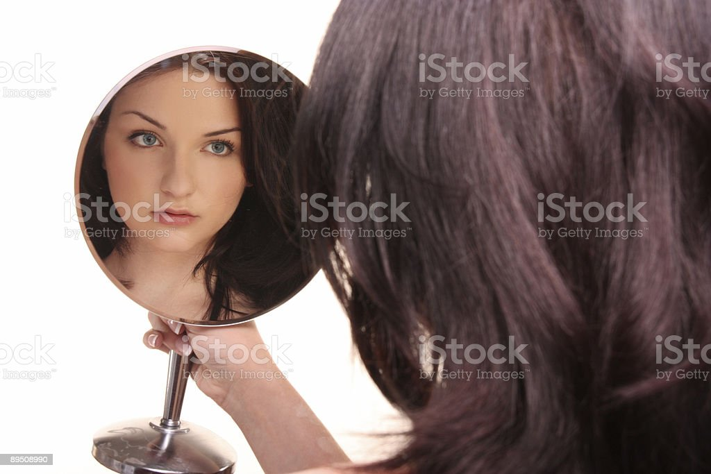 Beautiful brunette looking in mirror royalty-free stock photo