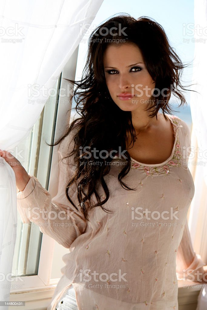 Beautiful brunette model at a beach house window royalty-free stock photo