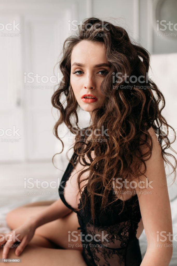 Beautiful brunette model with perfect body sitting on a bed in black lace underwear. stock photo