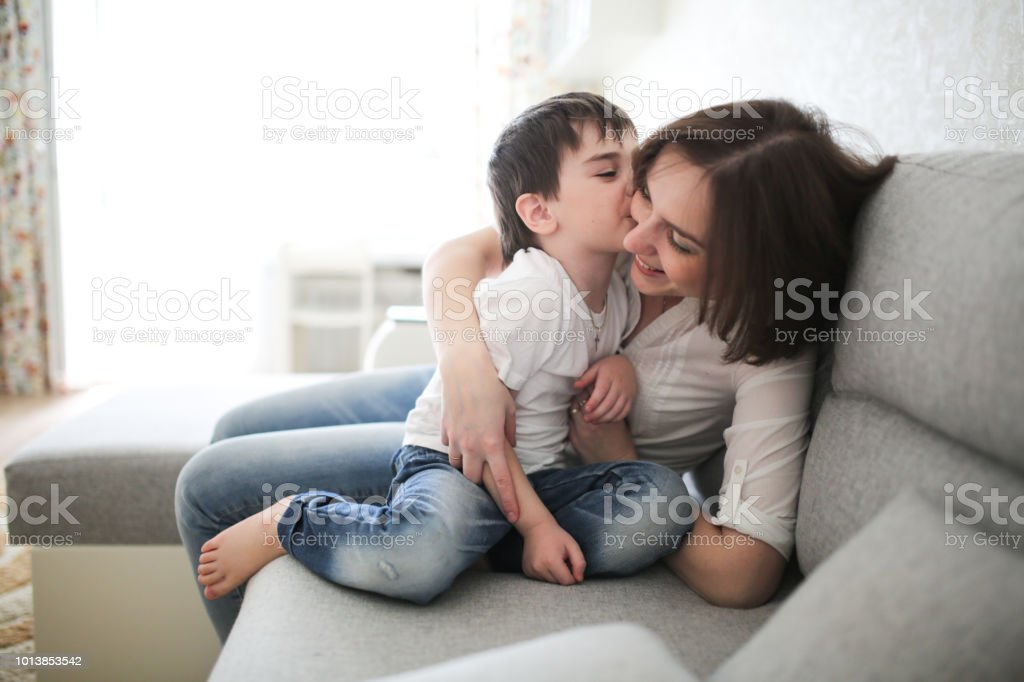Beautiful Brunette Mom And Son Hugging On Sofa Royalty Free Stock Photo