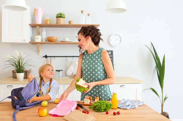 vacker brunett mor och hennes dotter packning hälsosam lunch och förbereda skol väska - lunchlåda bildbanksfoton och bilder
