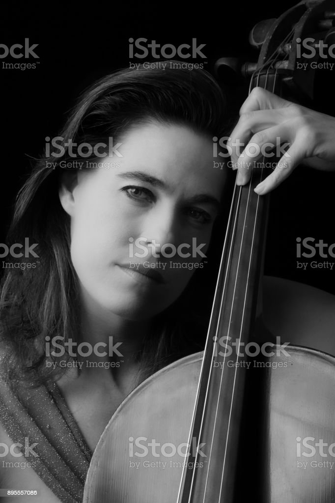 Beautiful Brunette Playing A Cello With Selective Light In Red Dress