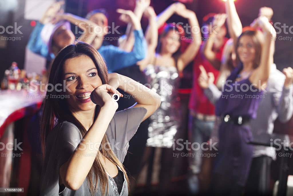 Beautiful brunette singing with the microphone in a club. royalty-free stock photo