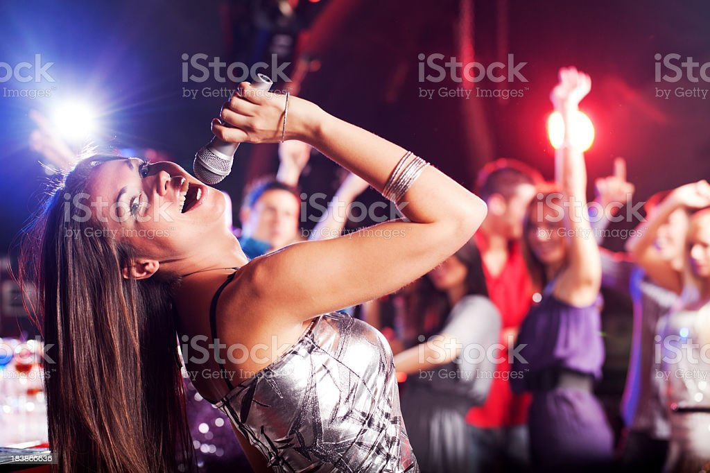 Beautiful brunette singing with the microphone in a club. stock photo