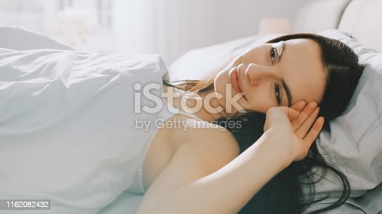 994789938 istock photo Beautiful Brunette Slowly Waking up in the Morning, Lying in a Bed, Smiles Charmingly. Sun Shines on a Happy Young Girl From the Big Window. 1162082432