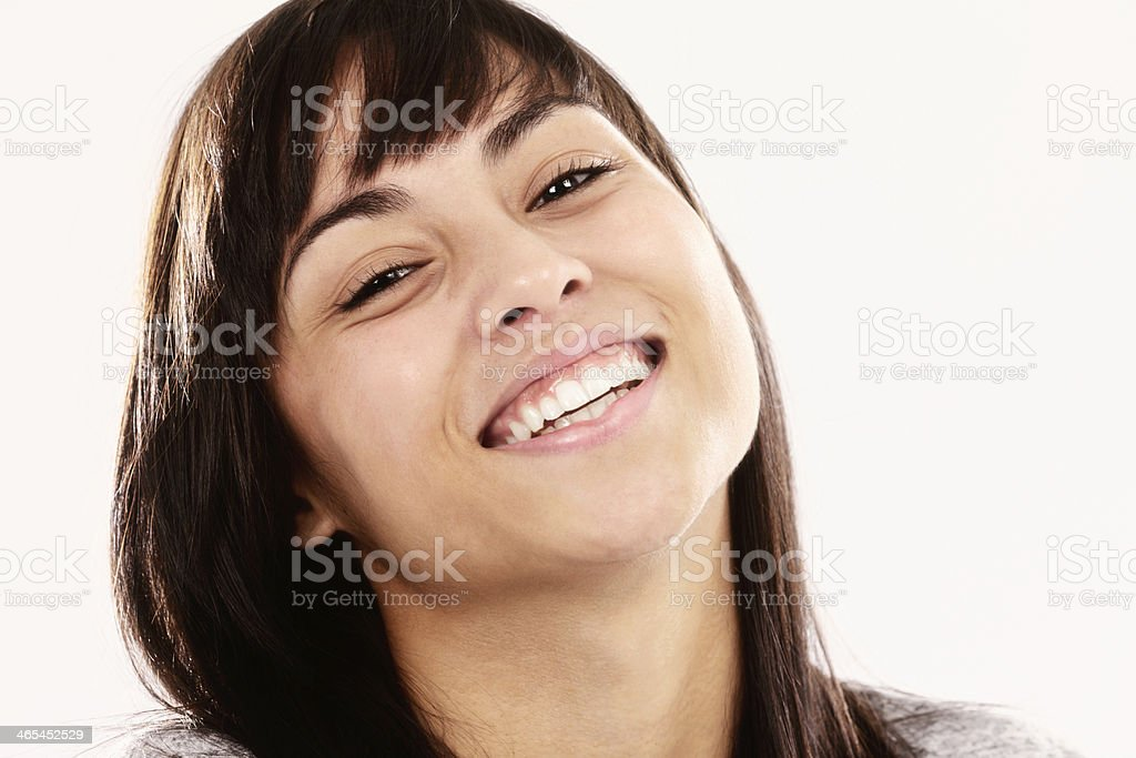 Beautiful brunette smiles happily, her head on one side royalty-free stock photo