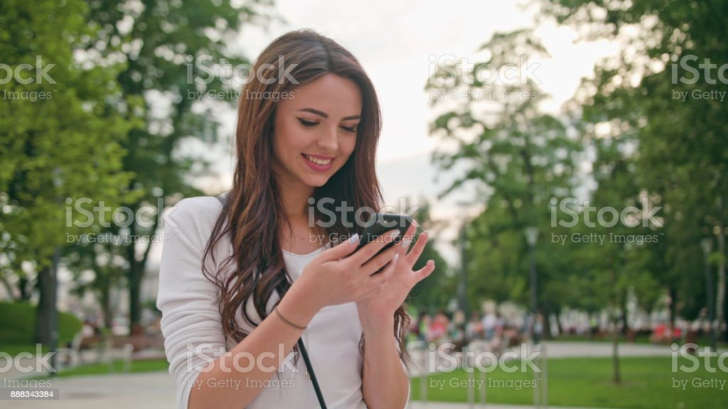 A Beautiful Brunette Using a Mobile Phone Outdoors - foto stock