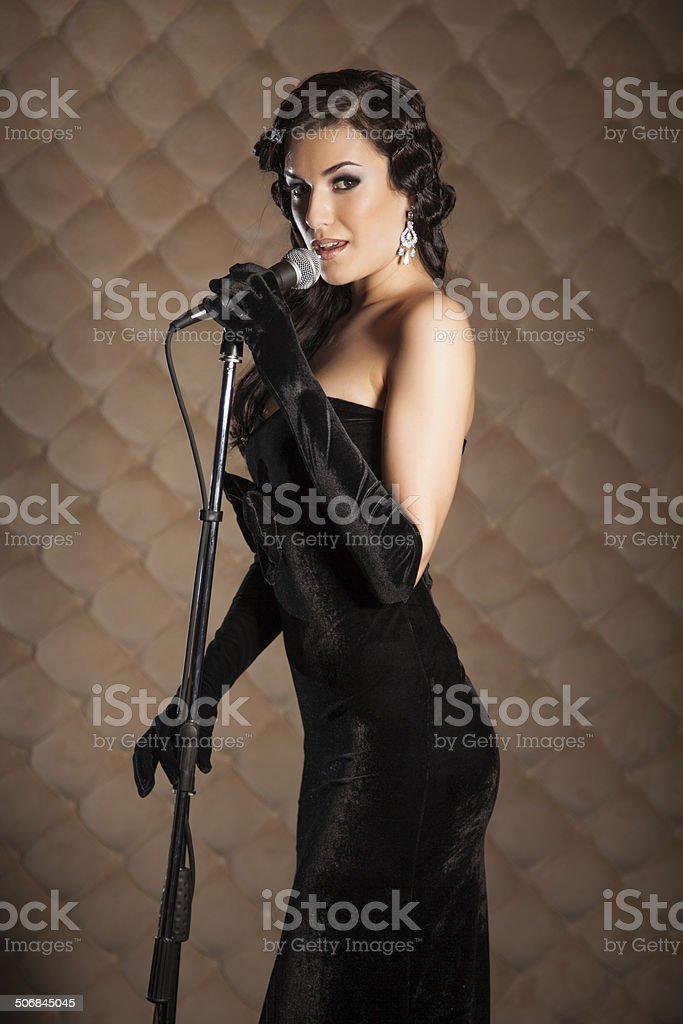 Beautiful brunette with a microphone sings a song on stage stock photo