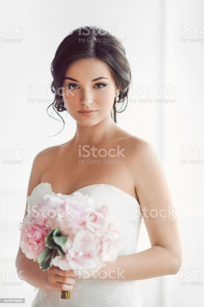 Beautiful brunette woman as bride with pink wedding bouquet on white stock photo