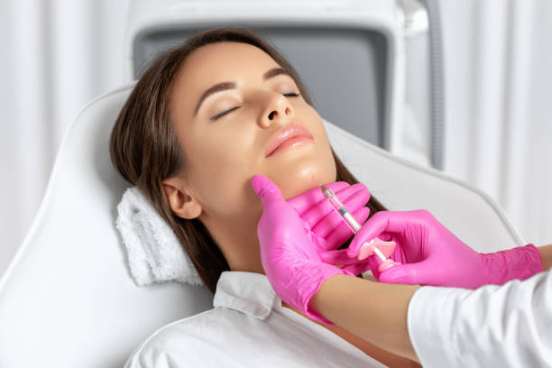 Beautiful brunette woman at the beautician.Cosmetologist does anti wrinkle injections on the chin against sagging skin. Women's cosmetology in the beauty salon. stock photo