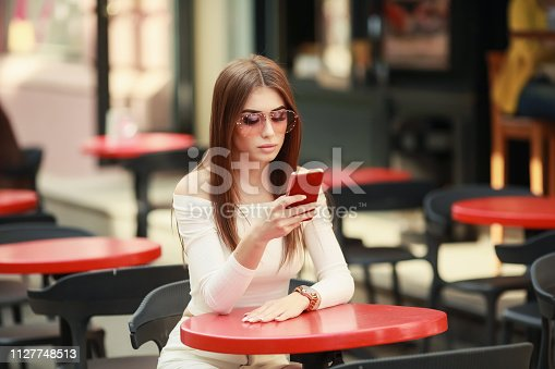 istock Beautiful brunette woman between palm leaves. Beauty summer make up photo.Close-up selfie-portrait attractive brunette girl with long hair,wear dress with palm print,sunglasses,Advertise your products 1127748513