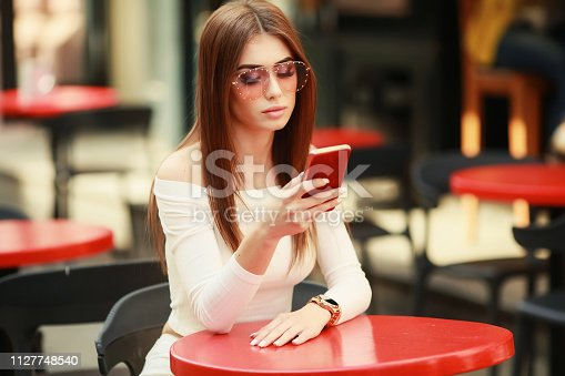 istock Beautiful brunette woman between palm leaves. Beauty summer make up photo.Close-up selfie-portrait attractive brunette girl with long hair,wear dress with palm print,sunglasses,Advertise your products 1127748540