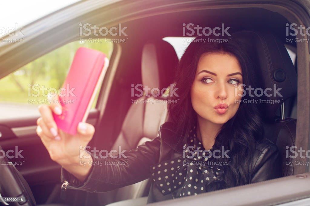 Beautiful brunette woman doing selfie in the car stock photo