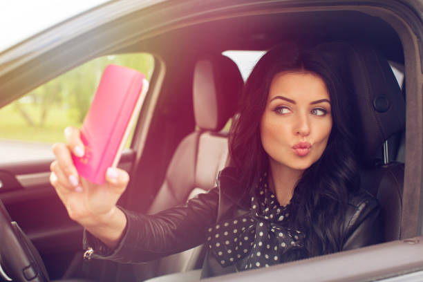 beautiful brunette woman doing selfie in the car - kiss стоковые фото и изображения