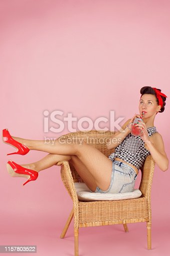Beautiful brunette woman drinking juice from a jar, pin-up style on a pink background.