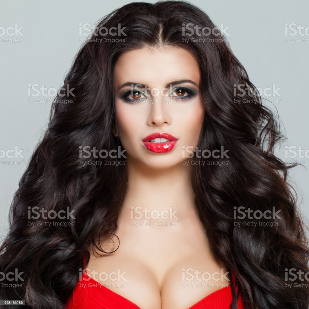 Beautiful Brunette Woman Fashion Model with Curly Hair, Red Lips Makeup and Red Bra stock photo