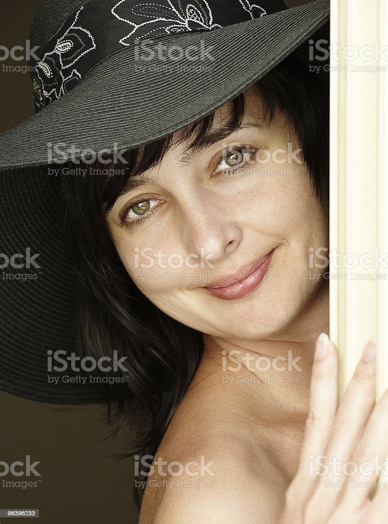 Beautiful brunette woman in hat looking from behind a curtain royalty-free stock photo