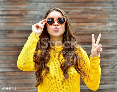 istock Beautiful brunette woman in sunglasses blowing lips kiss. wooden background. 609697712