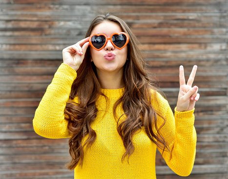 Beautiful smiling brunette woman in sunglasses blowing lips kiss over wooden background. Autumn time. Fall season.