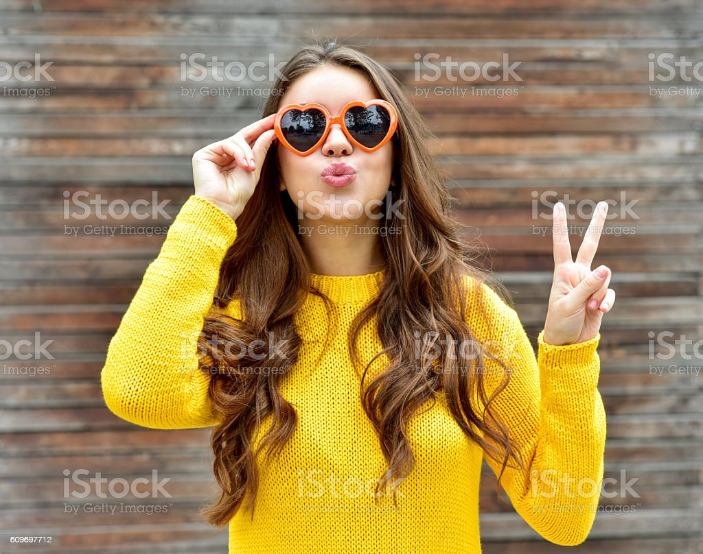 Beautiful brunette woman in sunglasses blowing lips kiss. wooden background. stock photo