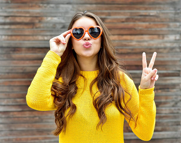 Beautiful brunette woman in sunglasses blowing lips kiss. wooden background. ストックフォト